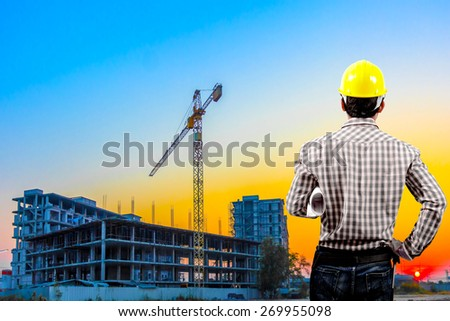 Engineer and blueprint for working at building construction site against beautiful sky sunset