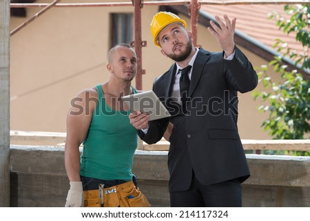 Engineer And Construction Worker Discussing A Project - Group Of Male Architect And Construction Worker On Construction Site - stock photo