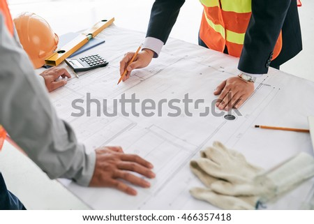 Engineer and contractor discussing draft on the table