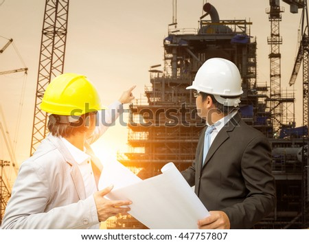 Engineer and foreman looking at blueprints.