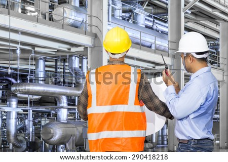 Engineer and foreman working with equipments and machinery in a industrial factory - stock photo