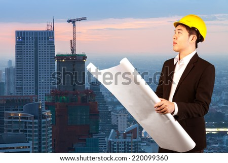 Engineer Architect with blueprint at the Construction site