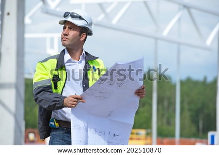 Engineer at construction site is inspecting works according to design drawings. - stock photo