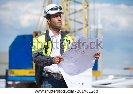 Engineer at construction site is inspecting works on site according to design drawings. - stock photo