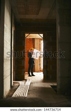Engineer at work in construction site, standing in apartment building and looking at blueprints and plans - stock photo