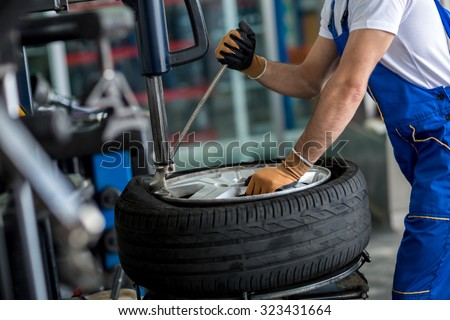 engineer  balancing  car wheel on balancer in workshop - stock photo