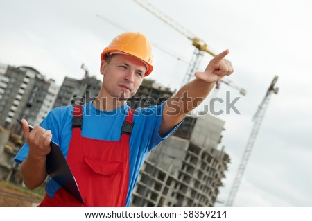 engineer builder at construction site directing up with finger - stock photo