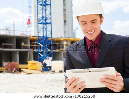 Engineer builder holding digital tablet at construction site - stock photo