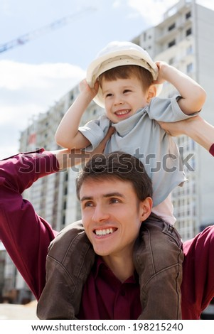 Engineer builder holding his son at construction site - stock photo