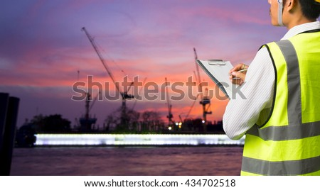 Engineer builder wearing safety vest with blueprint at construction site - stock photo