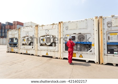 Engineer checking equipment in control system of reefer container box at yard