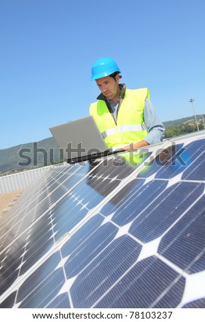 Engineer checking photovoltaic installation - stock photo
