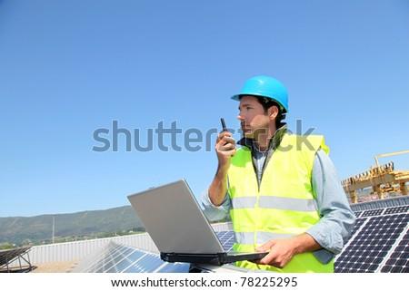 Engineer checking photovoltaic installation - stock photo