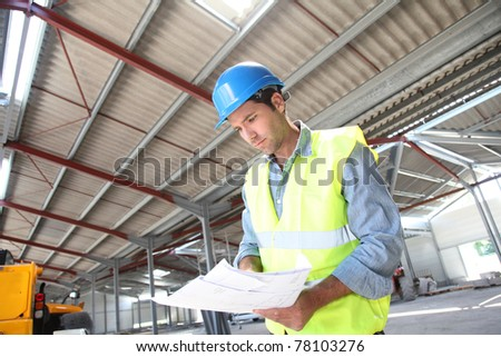 Engineer checking plan in building under construction - stock photo