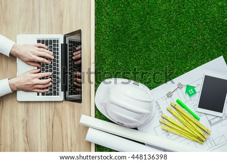 Engineer designing a green sustainable house and using a laptop, desktop with house project, folding meter and safety helmet, top view - stock photo