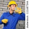 Engineer Drinking Water Near Brick Wall - stock photo