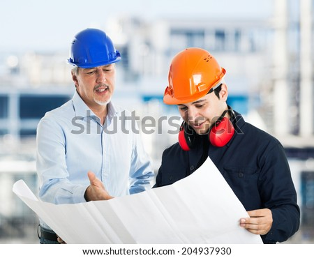 Engineer explaining a drawing to a worker - stock photo