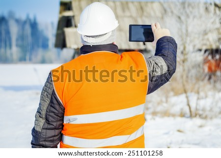 Engineer filmed with tablet PC destroyed building  - stock photo