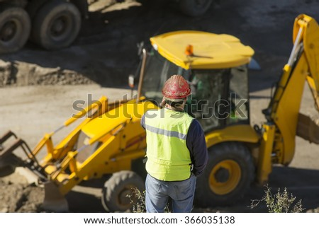 engineer foreman in highway construction site with excavators and trucks selective focus - stock photo