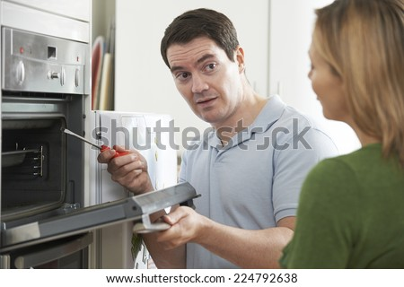 Engineer Giving Woman Advice On Kitchen Repair - stock photo