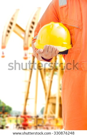 engineer hand holding yellow helmet for workers against pump jack background. oil and gas process - stock photo