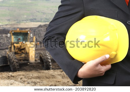 engineer hand holding yellow helmet for workers security against the background a large Graders