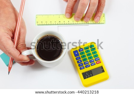 Engineer hands holding a cup of coffee and a ruler - stock photo