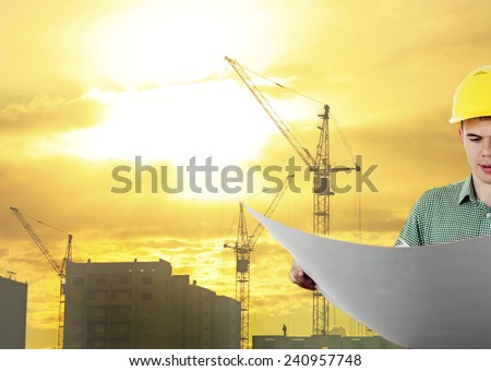 engineer hold blue print paper document wear helmet for workers security on background of new highrise buildings construction cranes on background evening sunset cloudy sky Silhouette Crane lifts load - stock photo