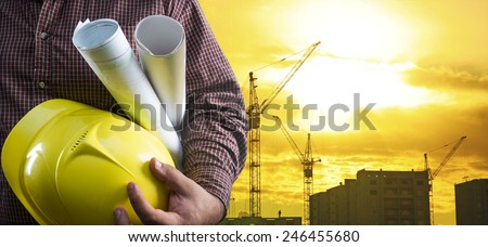 engineer hold yellow helmet for worker security blue print paper document on background of highrise apartment buildings and construction cranes on background of sunset sky Silhouette Crane lifts load - stock photo