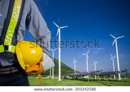 Engineer holding a yellow helmet. Against a backdrop of renewable energy farms. - stock photo