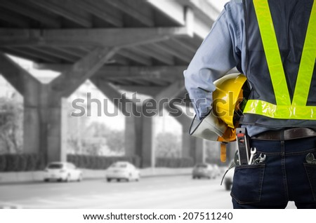 Engineer holding a yellow helmet for the safety of the workers, with expressway as a backdrop  - stock photo