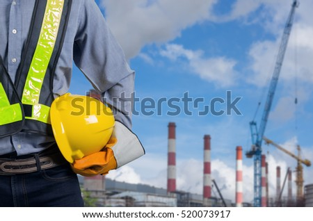 engineer holding a yellow helmet with a coal power plant in the background - Power Plant Engineer
