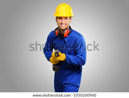 Engineer Holding Drill Machine On Grey Background