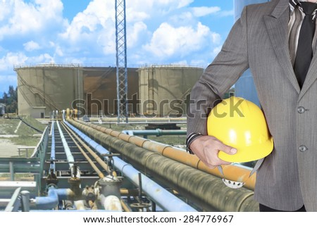 Engineer holding hardhat for working at pipe line connection to oil tanks in petrochemical oil refinery