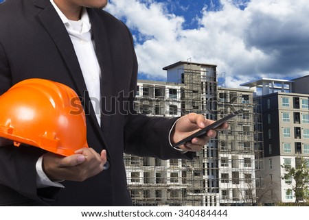 engineer holding helmet for working at footing of building construction site - stock photo