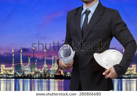 Engineer holding helmet for working at oil refinery petrochemical industrial plant at twilight - stock photo