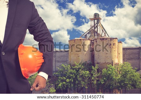 engineer holding helmet working at high building construction site against blue sky with in concept ecology and real estate vintage color - stock photo