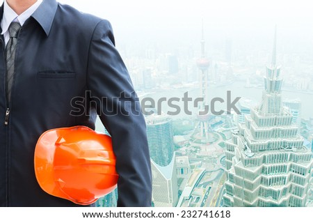 Engineer holding helmet  working at high building construction site against urban scene balcony overlooking city. - stock photo