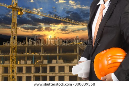 engineer holding orange helmet for workers security on background of new highrise apartment buildings and construction cranes on background of evening sunset cloudy sky Silhouette Crane lifts load - stock photo