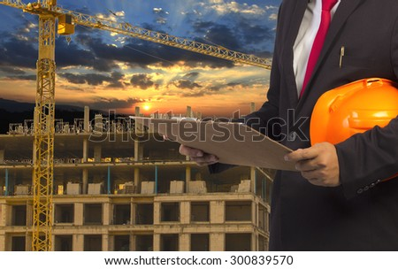 engineer holding orange helmet for workers security on background of new highrise apartment buildings and construction cranes on background of evening sunset cloudy sky Silhouette Crane lifts load