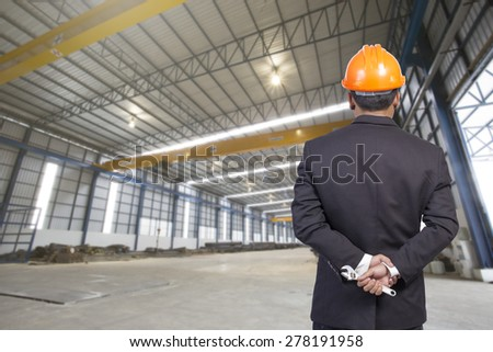 engineer holding orange helmet for workers security on factory background