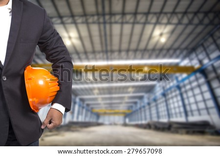 engineer holding orange helmet for workers security on factory background  apartm - stock photo