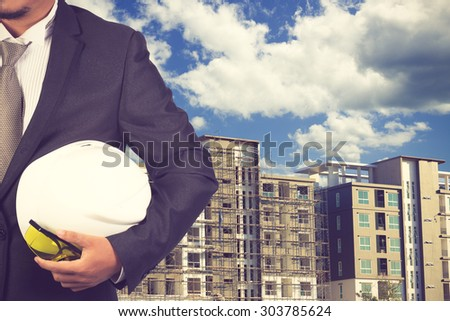 engineer holding white helmet for workers security on background of new highrise apartment buildings and construction background of blue sky vintage color - stock photo