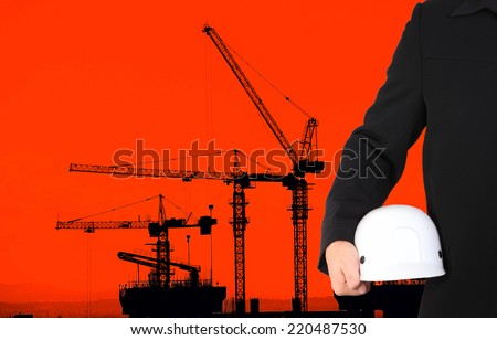 engineer holding white helmet standing in front of site working area  - stock photo
