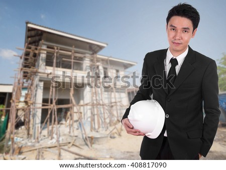 engineer holding white helmet with house construction background - stock photo