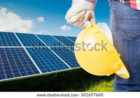 Engineer holding yellow construction helmet on solar power panels background - stock photo