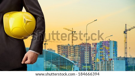 engineer holding yellow helmet against a background of new highrise apartment buildings and construction cranes. - stock photo