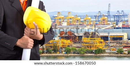 engineer holding yellow helmet and plan for workers security on background of harbor on background  - stock photo