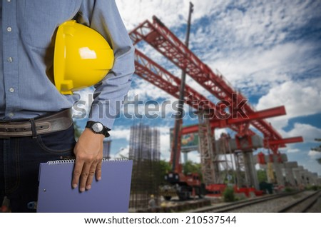 Engineer holding yellow helmet for workers security on background of construction cranes  lifts load. - stock photo