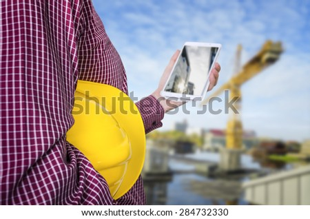 Engineer holding yellow helmet for workers security with construction site background. Selective focus on helmet.